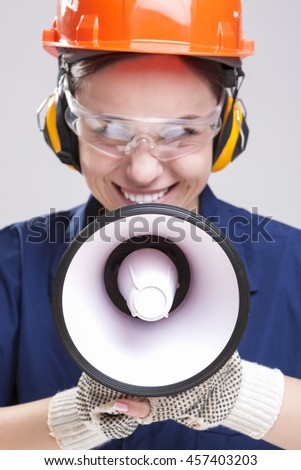 Expressive Caucasian Female Worker Posing with Megaphone and Wearing Hardhat for Protection. Vertical Image Composition - stock photo