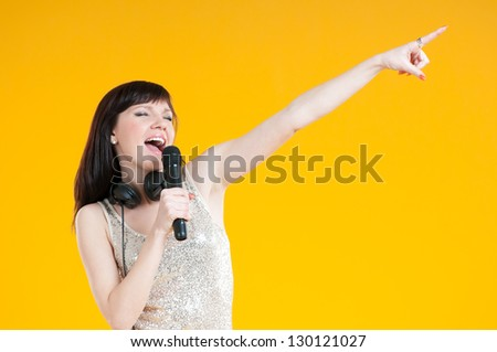 Expressive girl singing with a mike, yellow background - stock photo