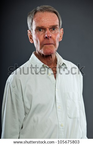 Expressive good looking senior man against grey wall. Funny and characteristic. Well dressed. Studio shot. - stock photo