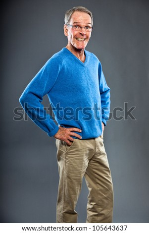 Expressive good looking senior man against grey wall. Funny and characteristic. Well dressed. Blue sweater. Studio shot. - stock photo