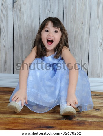 expressive little girl in dress sitting on floor with eyes and mouth wide open - stock photo