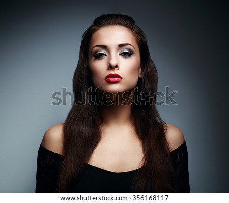 Expressive makeup female model with red lipstick and long hair posing on dark background. Closeup art portrait - stock photo