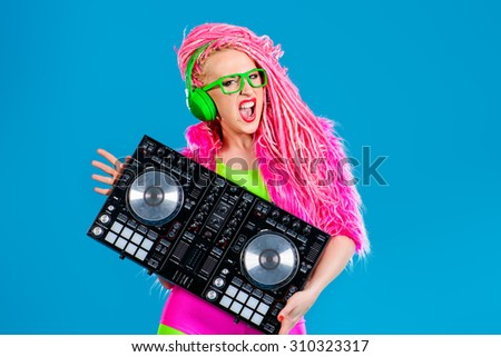 Expressive modern DJ girl wearing bright clothes, headphones and bright dreadlocks mixing up some music. Disco, party. Modern generation.  - stock photo