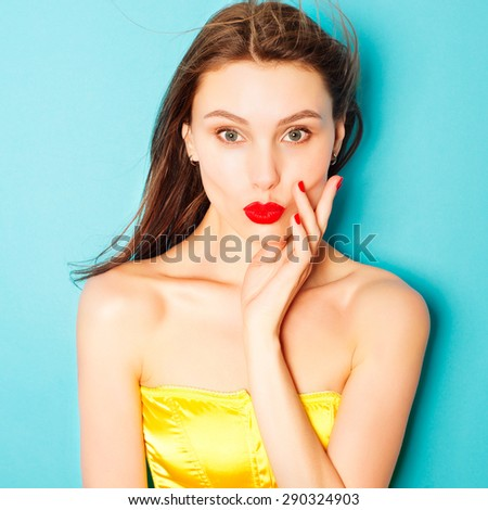 Expressive portrait of a beautiful brunette woman in the studio on a blue background, showing a kiss, the concept of beauty - stock photo