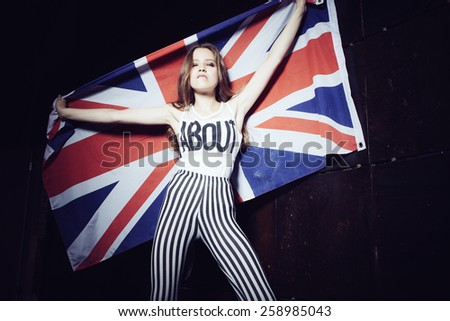 Expressive portrait of a beautiful girl with a British flag - stock photo