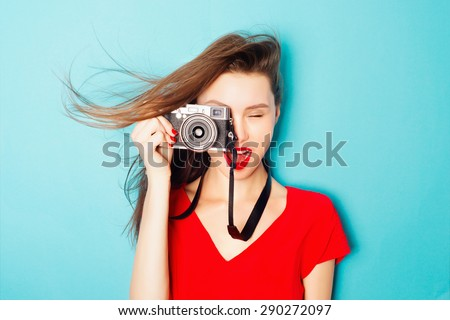 Expressive portrait of a beautiful young brunette woman in a red dress in the studio on a blue background with a camera in his hands - stock photo