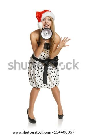 Expressive Santa girl shouting Xmas news through the megaphone. Full length female wearing Santa hat with loudspeaker, isolated on white background - stock photo