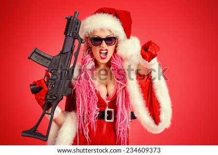 Expressive sexy babe dressed as Santa Claus standing with a gun over red background. Christmas. - stock photo