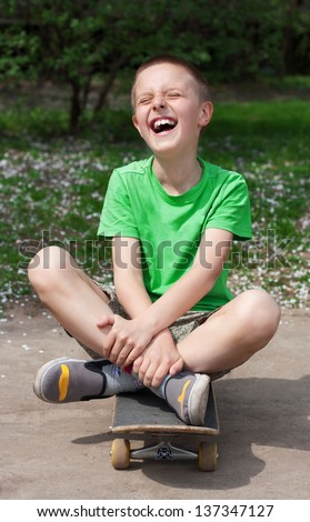 Expressive smiling boy sits cross-legged on a skateboard in park - stock photo