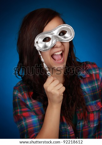 expressive teen girl hiding behind a silver mask, blue background - stock photo