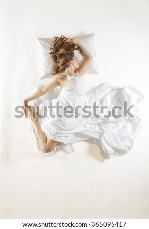 Expressive woman sleeping. Full length high angle view of a young woman sleeping on white background. Expressive woman in action, dreaming concept. Ballet dancer rehearsing in her sleep - stock photo