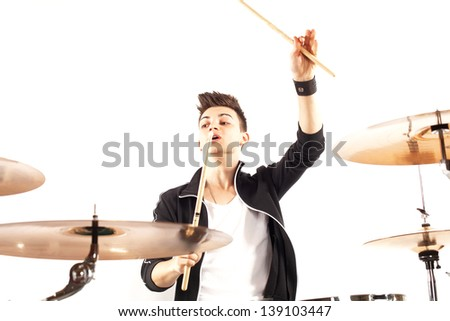 Expressive young drummer playing at the drums with drum stick - stock photo