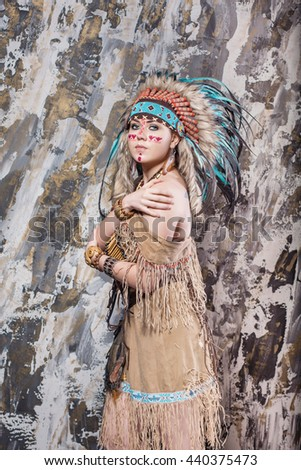 Expressive young girl with a pattern on the face and feathers and Roach looks directly into ethnic national style North American Indian background hairstyle and makeup - stock photo