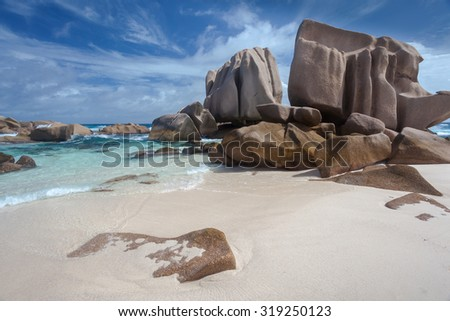 Exquisite Granite Boulders Overlooking A Stunning Tropical Turquoise Lagoon On A Beautiful White Sandy Beach On The Island Of La Digue In The Seychelles - stock photo