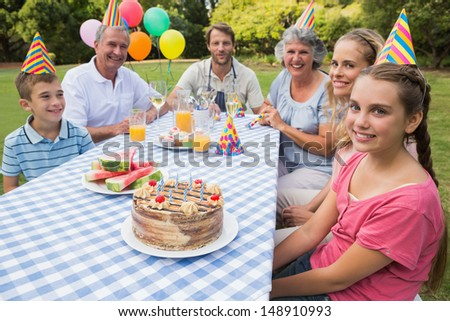 Extended family celebrating little girls birthday outside at picnic table smiling at camera - stock photo