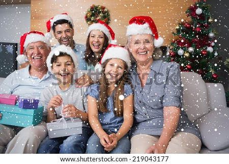 Extended family in Christmas hats with gift boxes in living room against snow falling - stock photo