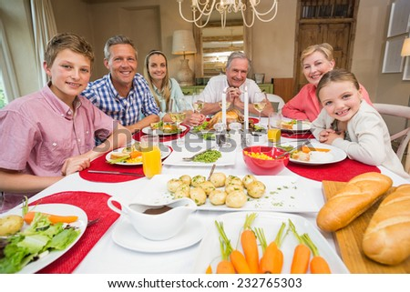 Extended family looking at camera at christmas time at home in the living room - stock photo