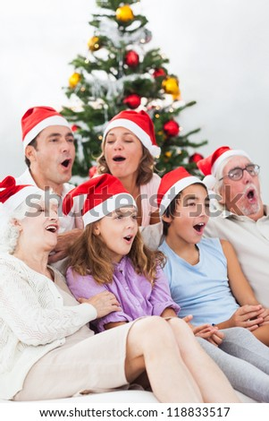 Extended family singing christmas carols together on couch - stock photo