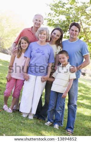 Extended family standing in park holding hands and smiling - stock photo