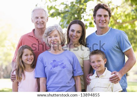 Extended family standing in park smiling - stock photo