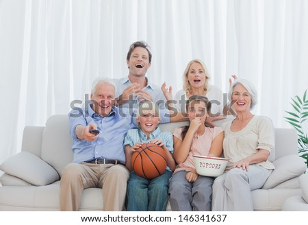 Extended family watching the television on couch - stock photo