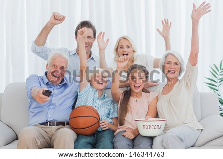 Extended family watching the tv on sofa - stock photo