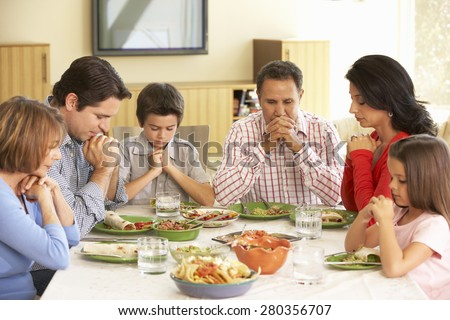 Extended Hispanic Family Saying Prayers Before Meal At Home - stock photo