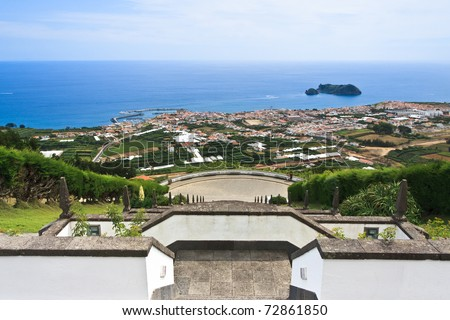 Extensive view from the church stairs down to the village and far out to sea. (Nossa Senhora da Paz church and village of Vila Franca do Campo in Sao Miguel island, Azores.) - stock photo