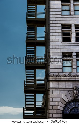 exterior detail of old office building and fire escape stairs - stock photo