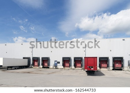 exterior of a large warehouse with several loading docks and trailers in front - stock photo
