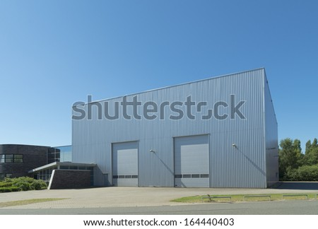 exterior of a modern warehouse with double roller doors - stock photo
