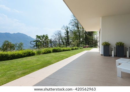 exterior of a new house, veranda with green lawn - stock photo