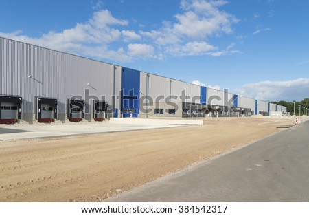 exterior of a newly build warehouse with loading docks - stock photo