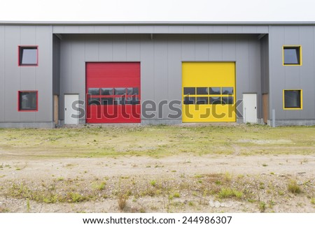 exterior of a newly build warehouse with red and yellow roller doors - stock photo