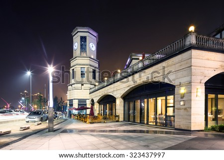 exterior of a vintage shopping mall at night - stock photo