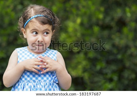 Exterior photo, 3 year old girl with mischievous expression - stock photo