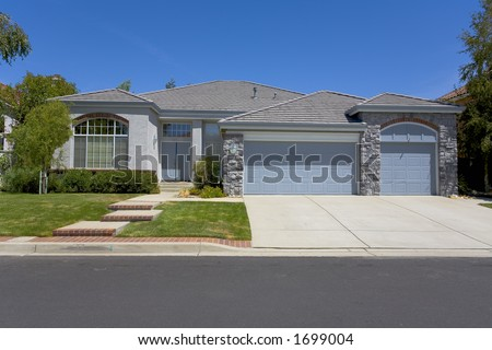 Exterior shot of a grey single story home with nice masonry. - stock photo