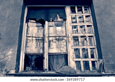 Exterior shot of an old, damaged, broken window in black and white. Monochrome image filtered in faded, retro, vintage style with red filter and soft focus. - stock photo