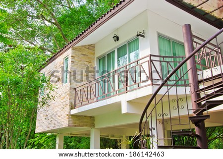 Exterior shot with crazy paving and plants with view into bedroom - stock photo