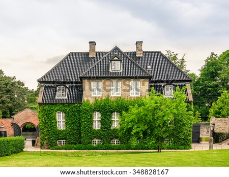 Exterior three-story house of light brick with a brown tiled roof. The facade of the house are entwined with green ivy and hedges, Copenhagen, Denmark - stock photo