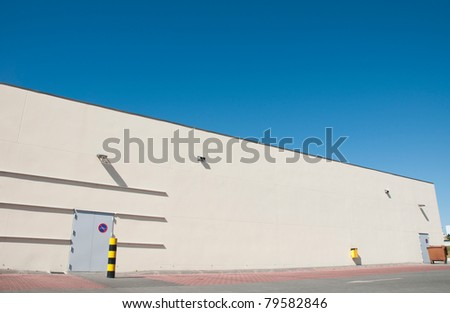 exterior view of a industrial warehouse building with a gorgeous blue sky - stock photo