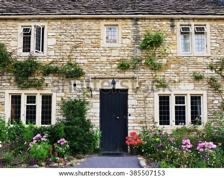 Exterior View of an Beautiful Old English House Surrounded with Flowers and Plants - stock photo