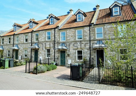 Exterior View of Terraced Stone Cottages on a Street in a Typical English Town - stock photo