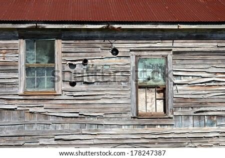 Exterior Wall Of A Grungy, Abandoned Wooden House With Windows And A Rusty Tin Roof - stock photo
