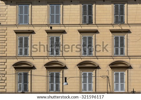 Exterior yellow wall of old building with windows and shutters, a background - stock photo