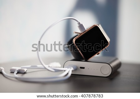 External battery charger, portable power bank, charging modern smart watch with energy through usb cable. Neutral colors - stock photo