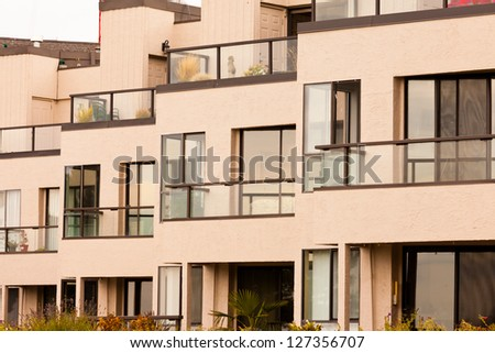 External facade of contemporary residential apartment block development with large glass windows and balconies for every unit. - stock photo