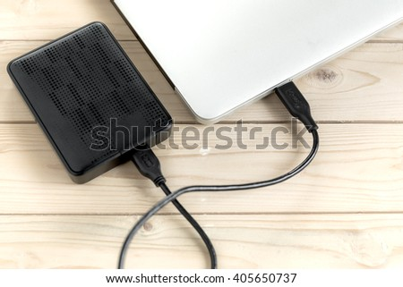 External hard drive connected to laptop computer, External hard disk and laptop computer, selective focus - stock photo