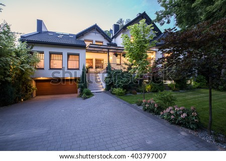 External view of contemporary white mansion with lawn - stock photo