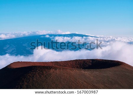 Extinct volcanic crater with Mauna Loa in background from Mauna Kea summit - stock photo